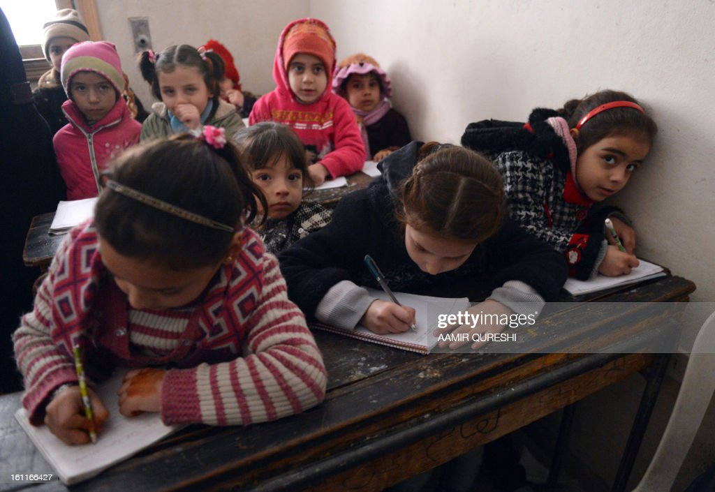 Syrian children attend a class at a school in the Kadi Askar area in the Syria's northern city of Aleppo on February 9, 2013. President Bashar al-Assad reshuffled his cabinet as regime warplanes raided rebel areas in a bid to end the stalemate in Syria's deadly civil war and hopes for a political solution appeared to founder. AFP PHOTO/AAMIR QURESHI