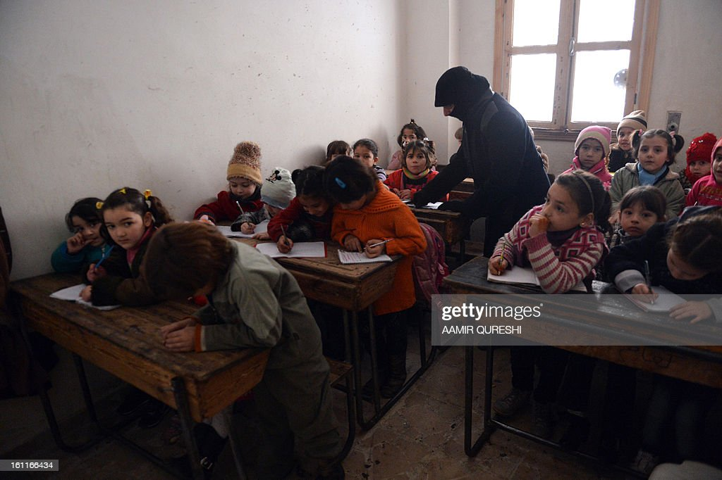 Syrian children attend a class at a school in the Kadi Askar area in the Syria's northern city of Aleppo on February 9, 2013. President Bashar al-Assad reshuffled his cabinet as regime warplanes raided rebel areas in a bid to end the stalemate in Syria's deadly civil war and hopes for a political solution appeared to founder.