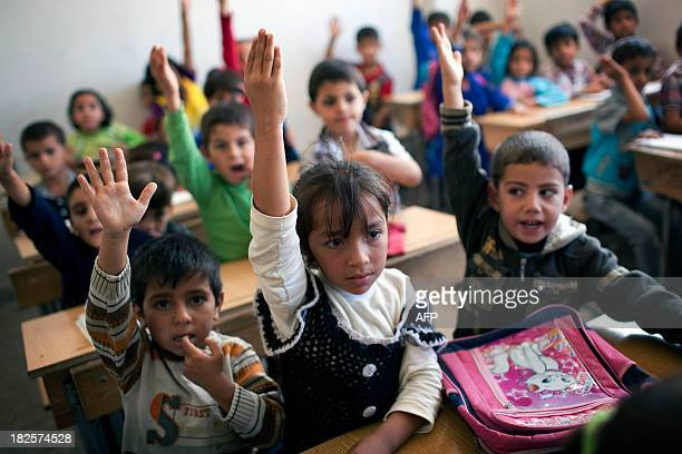 PAMPLIEGA Syrian children attend a class at a school in the Masai Hanano district in the northern Syrian city of Aleppo on September 23 2013 'The...