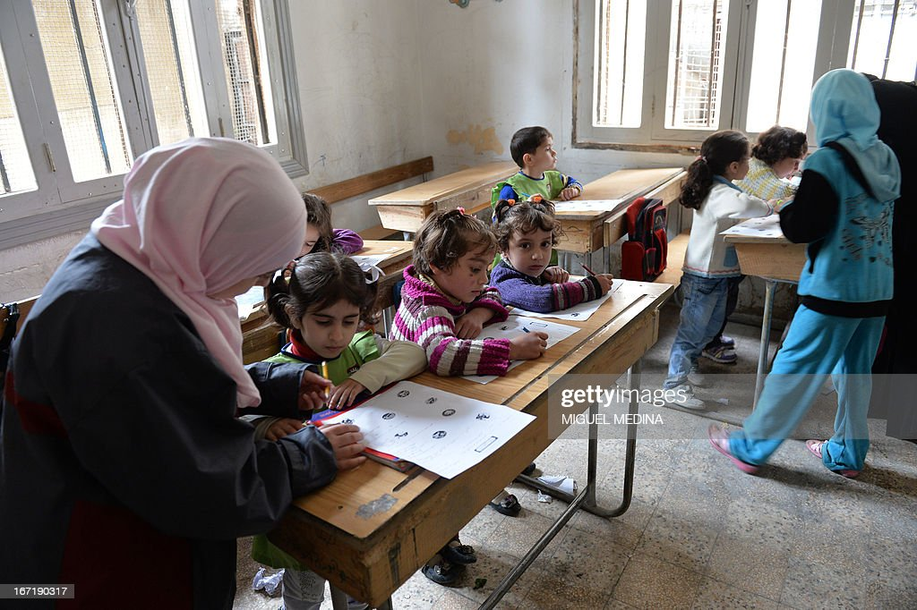 Syrian children attend a lesson at the Nur al-Haq school in the northern city of Aleppo on April 22, 2013. The European Union offered fresh aid to Syria's opposition, easing an EU oil embargo in favour of the rebels fighting President Bashar al-Assad, but stopping short of supplying offensive weapons.