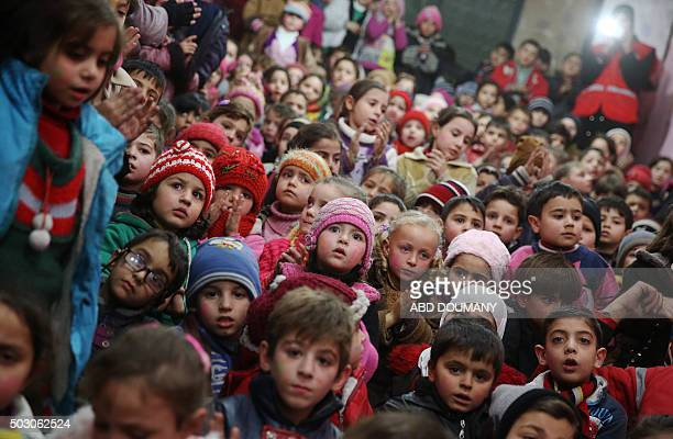 Syrian children attend an event organised by the Syrian Arab Red Crescent for New Year's eve celebrations in a rebelcontrolled area of Arbeen on the...