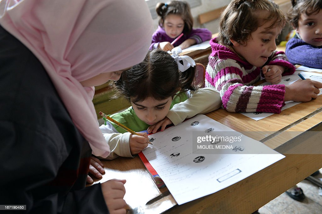 Syrian children attend class at the Nur al-Haq school in the northern city of Aleppo on April 22, 2013. The European Union offered fresh aid to Syria's opposition, easing an EU oil embargo in favour of the rebels fighting President Bashar al-Assad, but stopping short of supplying offensive weapons.