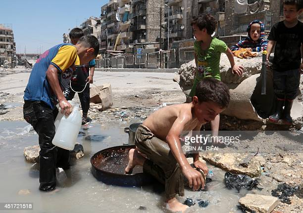 Syrian children collect buckets of stagnant murky water from the side of a road in a rebelheld area in the northern city of Aleppo on July 5 2014...