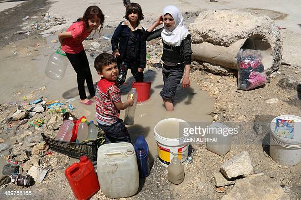 Syrian children collect buckets of stagnant murky water from the side of a road in a rebelheld area in the northern city of Aleppo on May 12 2014...