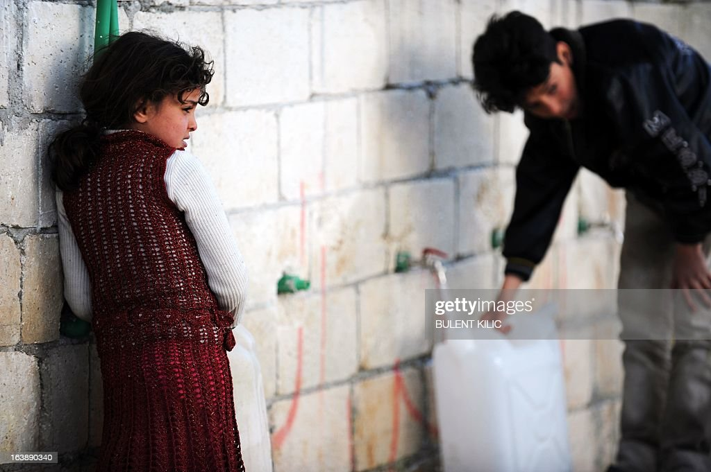 Syrian children collect water for their families at the refugee camp of Qah along the Turkish border in the village of Atme in the northwestern province of Idlib, on March 17, 2013. The conflict has killed at least 70,000 people, and forced more than one million Syrians to seek refuge abroad. Millions more have been internally displaced.