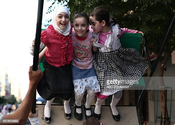 Syrian children enjoy a swing on the first day of EidalFitr which marks the end of the Muslim holy month of Ramadan on July 28 2014 in the besieged...