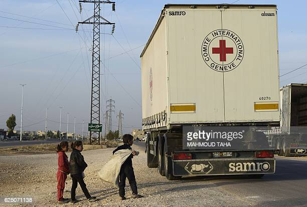 TOPSHOT Syrian children gather around a lorry after an aid convoy of the International Committee of the Red Cross and the Syrian Arab Red Crescent...