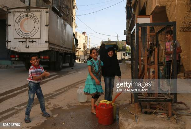 Syrian children laugh as they collect water near a Syrian Red Crescent truck carrying aid supplies in the rebel held and besieged town of Harasta in...