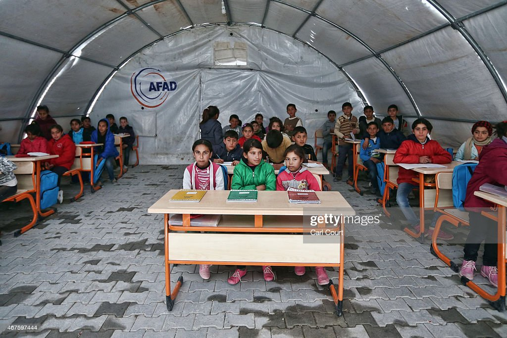 Syrian children listen to a teacher during a lesson in a temporary classroom in Suruc refugee camp on March 25, 2015 in Suruc, Turkey. The camp is the largest of its kind in Turkey with a population of around 35,000 Syrians who have fled the ongoing civil war in their country.
