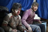 Syrian children look on as they wait for treatment following a reported air stike by regime forces at a makeshift clinic in the besieged rebel town...