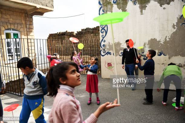 Syrian children perfom during a circus class on the roof top of a building on March 19 in Mardin There is laughter excitement and a sense of joyful...