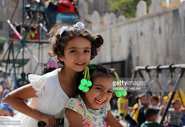 Syrian children play at an improvised playground in a rebelheld area of the northern city of Aleppo during the Eid alAdha holiday on September 24...