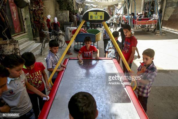 Syrian children play games at the childrens park installed by Civil defense during the Eid alFitr at Arbin town in Damascus Syria on June 27 2017