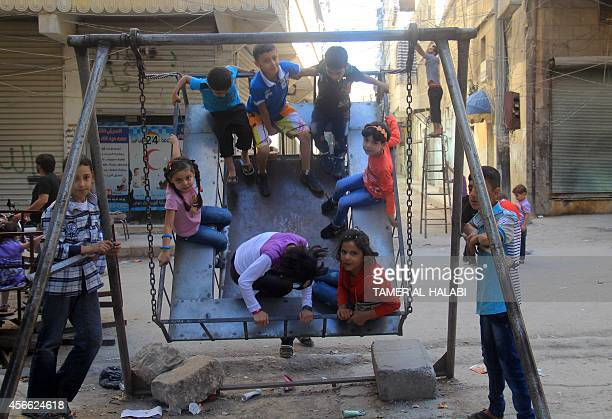 Syrian children play in a makeshift swing in Aleppo on October 4 on the first day of the Muslim holiday of Eid alAdha or Feast of the Sacrifice which...