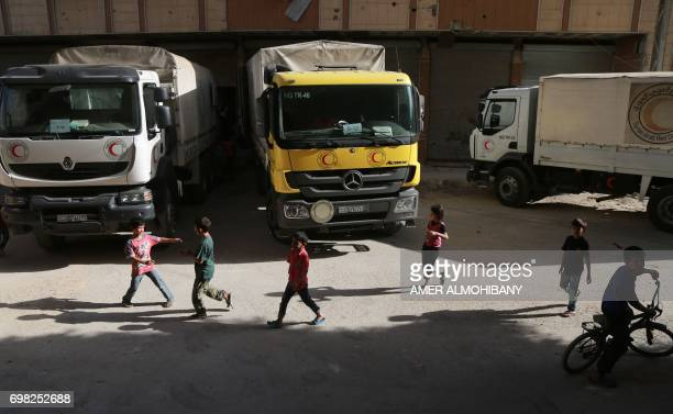 Syrian children play near Syrian Red Crescent trucks carrying aid supplies in the rebel held and besieged town of Harasta in the Eastern Ghouta...