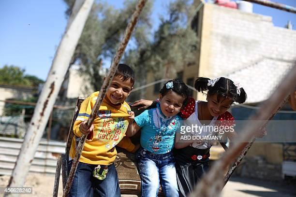 Syrian children play on a makeshift swing in the besieged rebel bastion of Douma northeast of the capital Damascus on October 4 on the first day of...