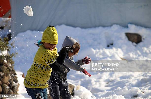Syrian children play with snow after a storm at a makeshift refugee camp near the village of Burayqah on the outskirts of southeastern Syrian border...