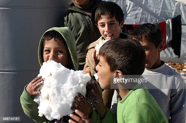 Syrian children play with the snow in the Arsal refugee camp in the Lebanese Bekaa valley on December 15 2013 Thousands of Syrian refugees living in...