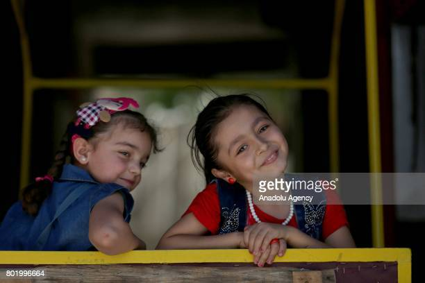 Syrian children pose for a photo at the childrens park installed by Civil defense during the Eid alFitr at Arbin town in Damascus Syria on June 27...