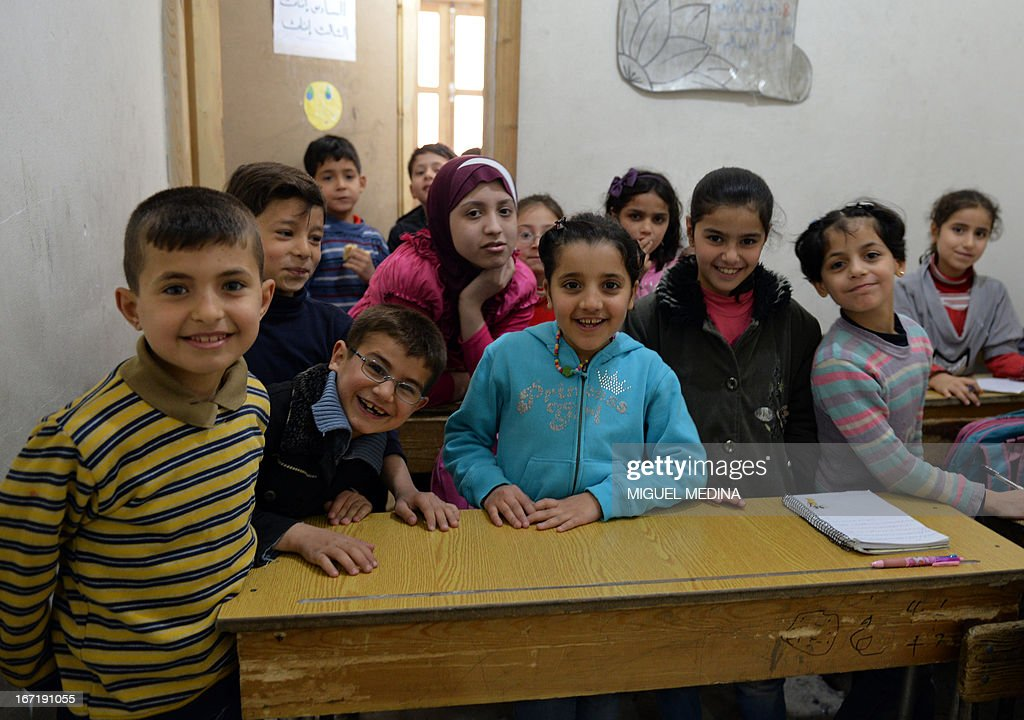 Syrian children pose for a picture as they attend class at a school in the northern city of Aleppo on April 22, 2013. The European Union offered fresh aid to Syria's opposition, easing an EU oil embargo in favour of the rebels fighting President Bashar al-Assad, but stopping short of supplying offensive weapons.