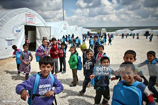 Syrian children react to the camera as they wait to attend lessons at a school in Suruc refugee camp on March 25 2015 in Suruc Turkey The camp is the...
