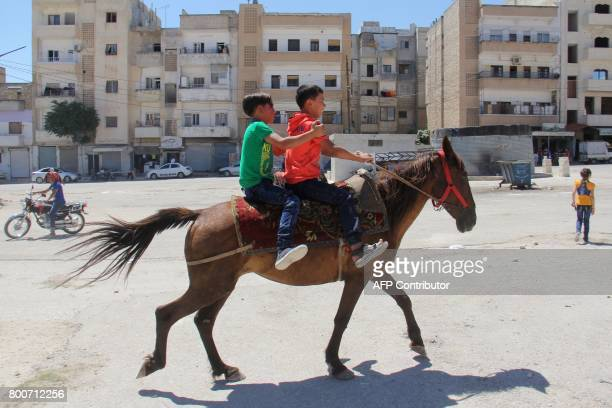 TOPSHOT Syrian children ride a horse in the northern city of Idlib on June 25 on the first day of Eid alFitr holidays which mark the end of the holy...