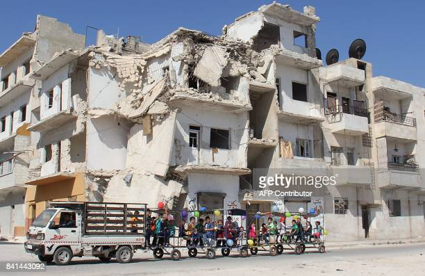 TOPSHOT Syrian children ride in carriages decorated in balloons along a damaged street in the northwestern Syrian city of Idlib on September 1 as...