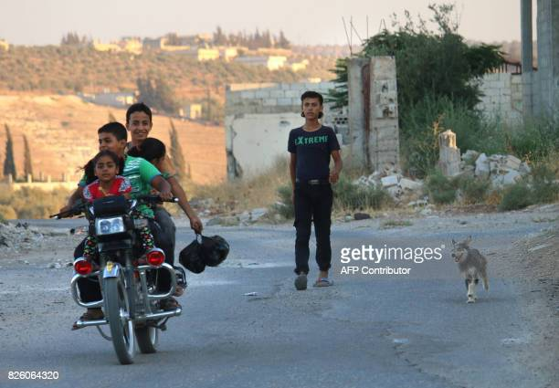 Syrian children ride on a motorcycle past a youth and a dog in a rebelheld area in the southern town of Daraa on August 3 2017 / AFP PHOTO / Mohamad...