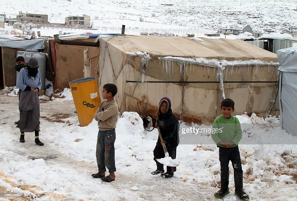 Syrian children shovel snow in a refugee camp in the town of Arsal in the Lebanese Bekaa valley on December 13, 2013. Thousands of Syrian refugees living in makeshift camps in Lebanon were weathered a winter storm that brought snow, rain and freezing temperatures to the country.