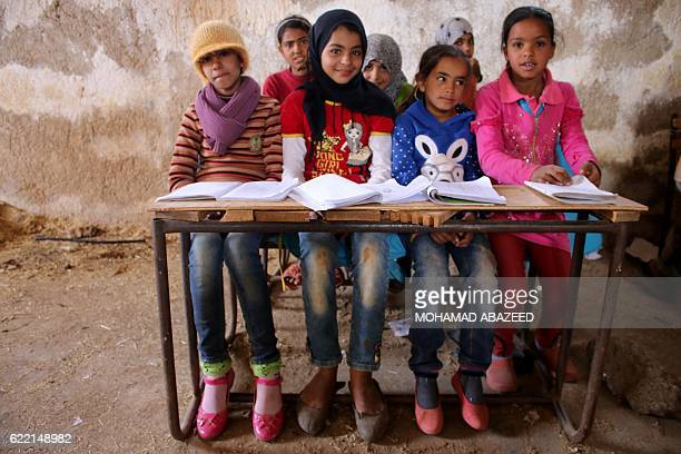 TOPSHOT Syrian children sit during class in a barn that has been converted into a makeshift school to teach internally displaced children from areas...