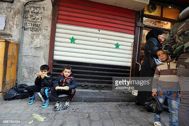 Syrian children sit in front of a door bearing the Syrian flag as they eat corn in the old part of the capital Damascus on November 26 2015 AFP PHOTO...