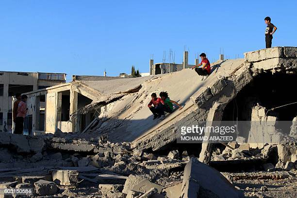 TOPSHOT Syrian children slide down rubble of destroyed a building in the rebelheld city of Daraa in southwestern Syria on September 12 2016 as...