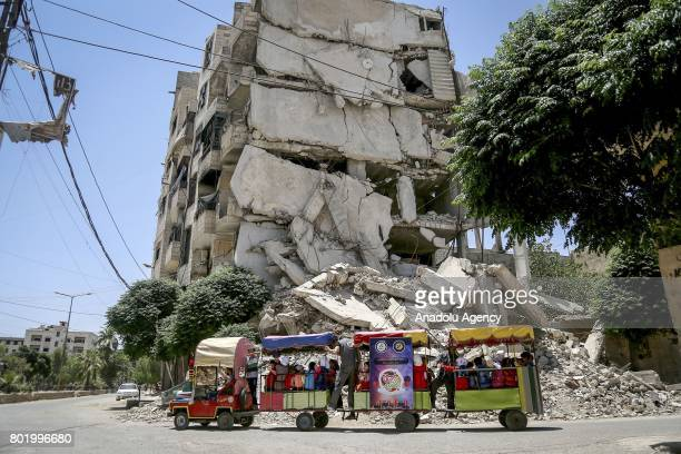 Syrian children tour with train around the collapsed buildings near the childrens park installed by Civil defense during the Eid alFitr at Arbin town...