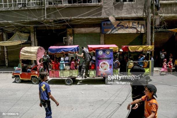 Syrian children tour with train at the childrens park installed by Civil defense during the Eid alFitr at Arbin town in Damascus Syria on June 27 2017