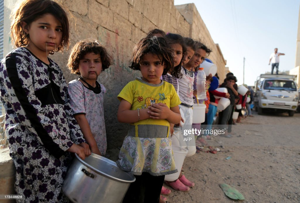 Syrian children wait in line to collect a free Iftar meal in the northern city of Raqqa during the Muslim holy month of Ramadan on July 14, 2013. The new head of the Syrian National Coalition Ahmad Jarba has backed calls for a truce from UN chief Ban Ki-Moon during the holy month of Ramadan. During Ramadan, Muslims the world over gather with family over festive meals after sunset when they can break the dawn-to-dusk fast.
