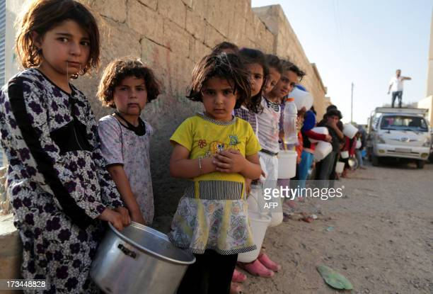 Syrian children wait in line to collect a free Iftar meal in the northern city of Raqqa during the Muslim holy month of Ramadan on July 14 2013 The...