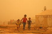 Syrian children walk amid the dust during a sandstorm on September 7 2015 at a refugee camp on the outskirts of the eastern Lebanese city of Baalbek...