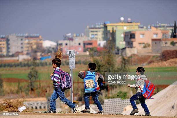Syrian children walk on the street after their school on January 18 2014 in Reyhanli near the town of Hatay southern Turkey UN refugee chief Antonio...
