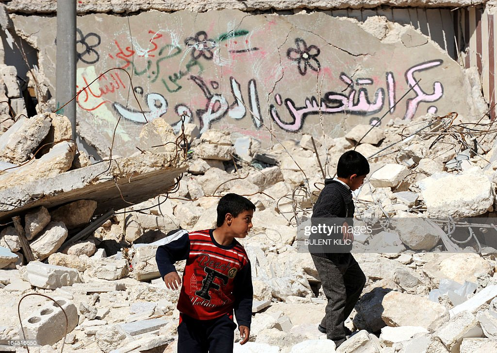 Syrian children walk past destroyed buildings in the northern city of Aleppo on March 24, 2013. Syria's mainstream insurgent Free Syrian Army does not recognise Ghassan Hitto, a rebel prime minister chosen by dissidents after hours of heated talks last week, a rebel official told AFP. Arabic writing on wall reads 'Tomorrow things will get better'. AFP PHOTO/BULENT KILIC