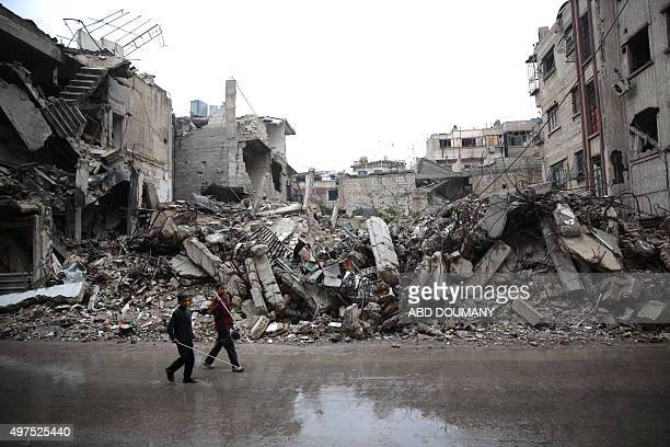 Syrian children walk past the rubble of destroyed buildings in the rebelheld area of Douma east of the Syrian capital Damascus on November 17 2015...