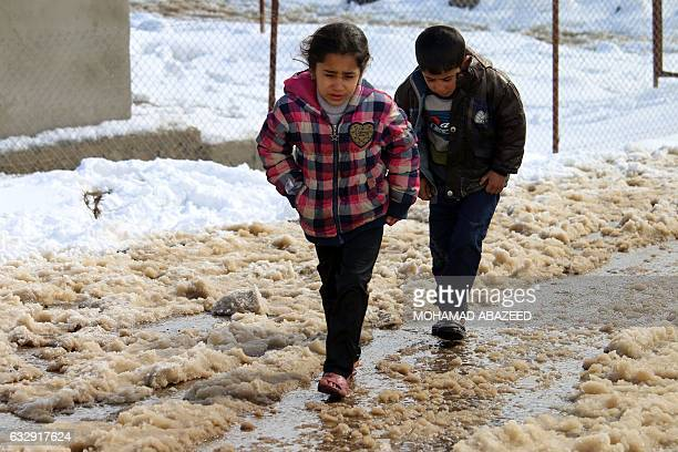 Syrian children wearing flip flops walk down a muddy path after a storm at a makeshift refugee camp near the village of Burayqah on the outskirts of...
