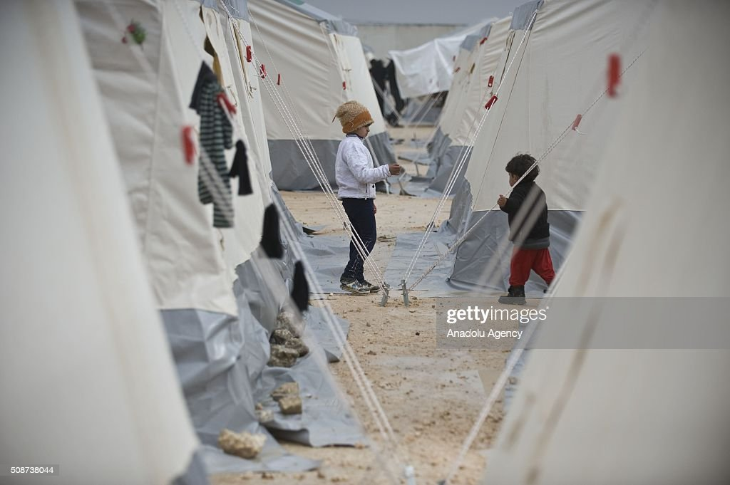Syrian children who fled bombing in Aleppo, are seen near tents, which were distributed by the IHH Humanitarian Relief Foundation, a Turkish NGO, at the Oncupinar crossing, opposite the Turkish province of Kilis, near Azaz town of Aleppo, Syria on February 6, 2016. Thousands of Syrians have massed on the Syrian side of the border seeking refuge in Turkey.