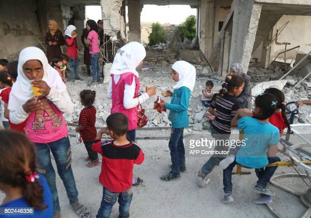 Syrian children who fled their homes in Ghouta's alMarj town play amidst the debris of buildings in the town of alNashabiyah in the eastern Ghouta...