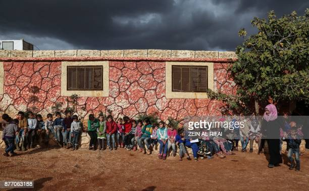 TOPSHOT Syrian children who lost their parents in the fighting sit outside an orphanage with a counsellor situated near the town on Sarmada close to...
