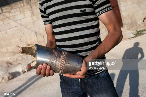 A Syrian citizen holds the remains of a projectile shot by a tank near the town of Khan Sheikhun which activists say is under heavy regime shelling...