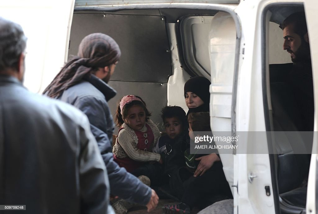 Syrian civil defence members evacuate a family following reported air strikes by regime forces on the Kafr Batna town in the rebel-held Eastern Ghouta area, on the outskirts of the capital Damascus, on February 12, 2016. / AFP / AMER ALMOHIBANY