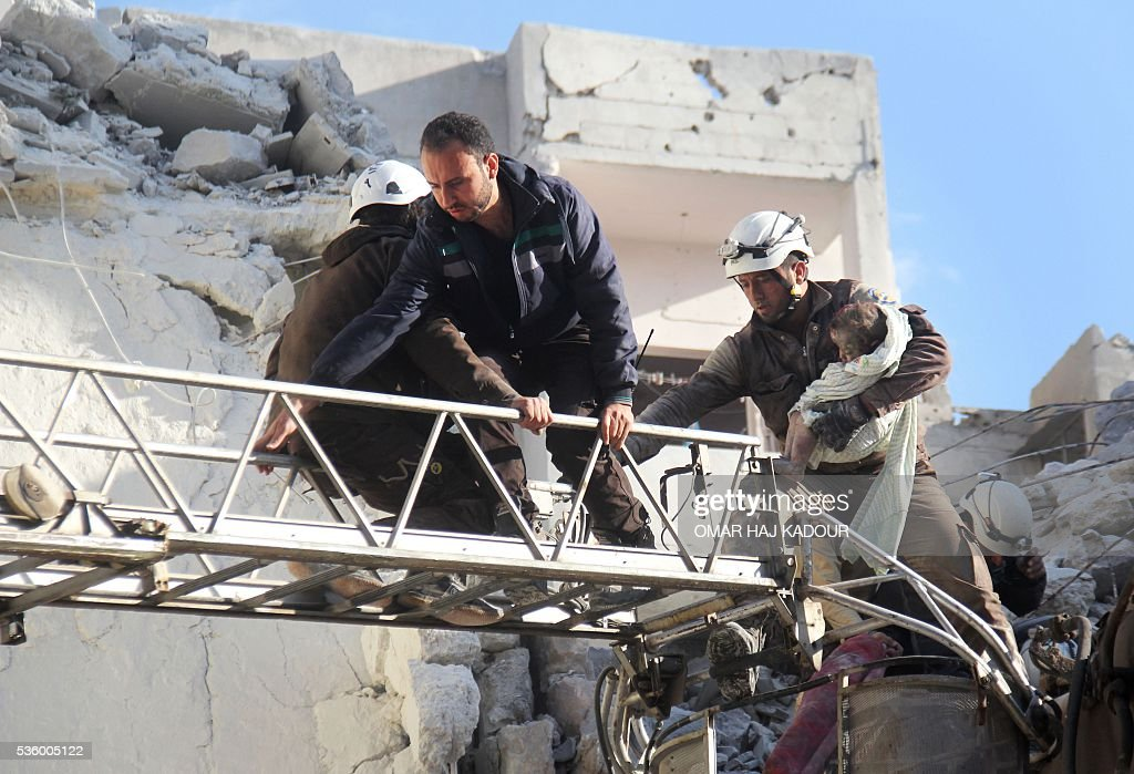 Syrian Civil Defence members evacuate a child from the rubble of buildings destroyed following Russian air strikes a day earlier on the northwestern city of Idlib, on May 31, 2016. / AFP / Omar haj kadour