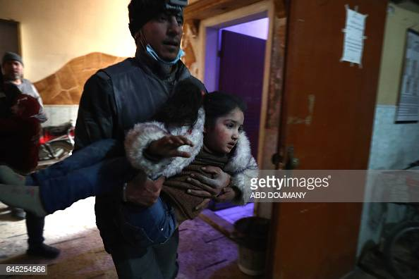 Syrian civil defence volunteer carries a wounded girl as he rushes into at a makeshift hospital following reported government airstrike on the...