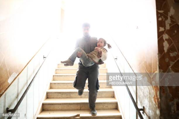 Syrian civil defence volunteer carries a wounded girl as he rushes to a makeshift hospital following reported government airstrike on the rebelheld...