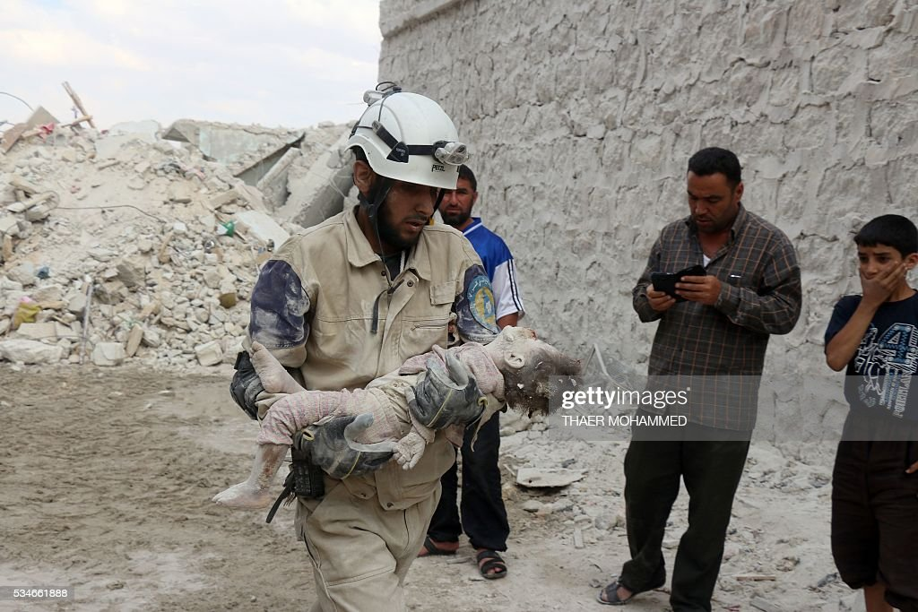 A Syrian civil defence volunteer carries the body of a child following a reported attack by Syrian government forces on May 27, 2016, in the Tariq al-Bab neighbourhood in the northern city of Aleppo. / AFP / THAER